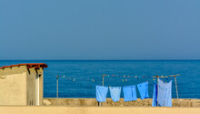 Small Hut At A Beach With Hanged Laundry And Deep Blue Sea Under Clear Sky In The Background