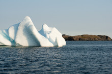 A Large White Iceberg Formation Floating In The Cold Ocean With Layers Of Textured Ice And Snow. The Ice Is In Transition Melting From The Warm Rays Of The Sun At Sunset. The Berg Is A Blocky Shape.