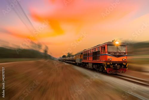 Fast speed motion cargo train on railway with twilight sun sky background. - fototapety na wymiar