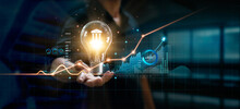 Businessman Holding Creative Light Bulb With Growth Graph And Banking Icons. Financial Innovation Technology Develop New Products And Services That Enhance Successful And Profit In Global Business.