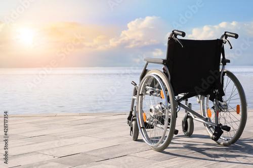 Tablou Canvas Empty modern wheelchair near river on embankment