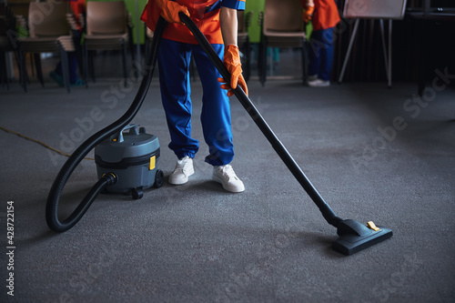 Obraz Cleaning lady using a canister vacuum cleaner - fototapety do salonu