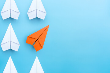 Business concept for new ideas creativity and innovative solution, Group of white paper plane in one direction and one orange paper plane pointing in different way on blue background