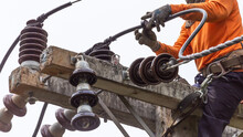 Rural Electric Poles Are Being Repaired By Electricians Installing Wires To Connect. The Tops Of The Electric Poles Are Attached To The Insulator. It Is A Job At A High Rate.