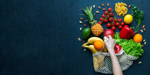 Human Hand Holding A String Bag With Fruits And Vegetables