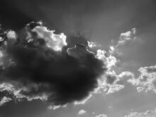 A Ray Of Sun Peeks Through A Dark Cloud. Dark Cloud In The Sky. Sun From A Cloud. Black And White Photo