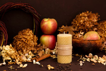 Beeswax Candle Made By Hand, Cinnamon, Apples And Dry Hydrangea Flowers On Brown Background. Honey Aroma For Interior And Tradition. Mockup, Front View.
