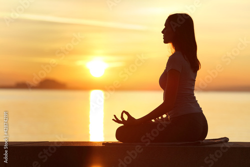 Vászonkép Profile of woman silhouette doing yoga exercise at sunset