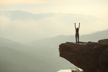 Woman Celebrating Raising Arms In The Mountain
