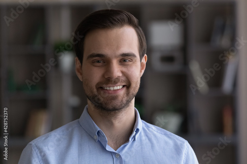 Fototapeta Headshot portrait of smiling young Caucasian man feel optimistic satisfied with employment or recruitment. Profile picture of happy millennial male renter or tenant pose in own house or apartment. obraz