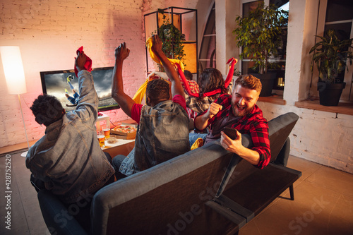 Group of friends watching TV, sport match together Fototapet