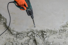 A Builder Dismantles A Perforator Drill Breaks The Concrete Floor At A Construction Site