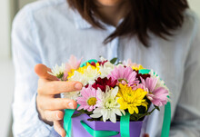 Young Woman Holding Beautiful Purple Basket Full Of Colorful Flowers In Her Hands. Celebration, Birthday Or Every Day Gift.