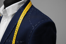 Semi-ready Jacket With Tailor's Measuring Tape On Mannequin Against Grey Background, Closeup