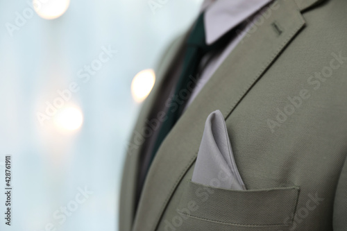 Tela Man with handkerchief in suit pocket against blurred lights, closeup