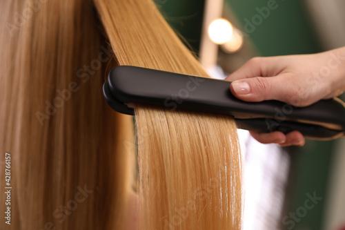 Obraz Stylist straightening woman's hair with flat iron in salon, closeup - fototapety do salonu