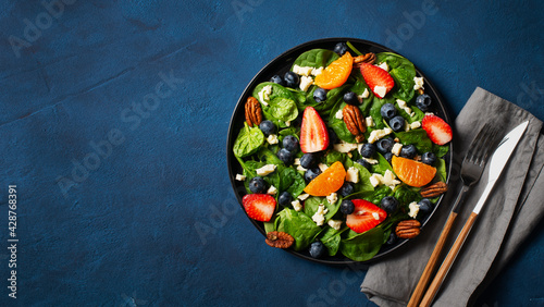 Fotografiet Summer salad with berries, cheese and spinach on blue background