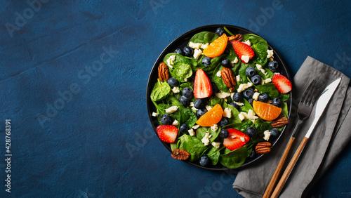 Billede på lærred Summer salad with berries, cheese and spinach on blue background
