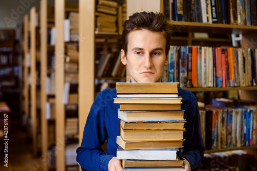 Fotografie, Tablou Male student with negative and bored mimic on his face holding a big stack of books in the library