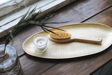 Details Of Interior, Aromatic Candle In Glass And Wooden Brush With Natural Bristles On Metal Tray On The Wooden Window Sill