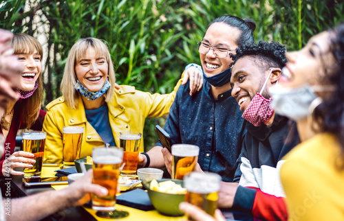 Young people drinking beer with opened face mask - New normal life style concept with millenial friends having fun together on happy hour at brewery garden party - Vivid filter with focus on asian guy - fototapety na wymiar
