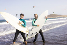 Full Length Portrait Of A Cheerful Young Couple Joking..Rock People. Friends Holding Surfboards As Guitars .