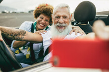 Trendy Senior Couple Having Fun In Convertible Car During In Summer Vacation - Joyful Elderly People Taking Selfie On Cabriolet Auto Outdoor With Mobile Phone