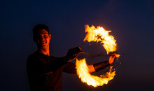 Game Of Light And Dark. Fire Spinner At Night. Happy Male Spinner Spin Burning Poi. Fire Performance. Poi Spinning And Flow Art. Evening Party. Outdoor Festival. Celebrating Holidays