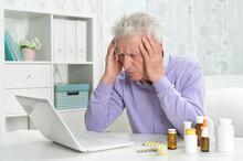 Portrait Of Sad Sick Senior Man Using Laptop
