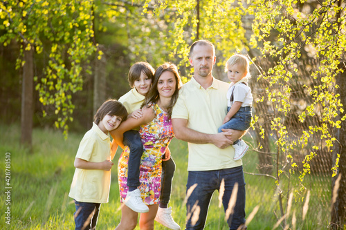 Beautiful family, mother, father and three kids, boys, having familly outdoors portrait taken on a sunny spring evening, beautiful blooming garden, sunset time