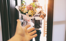 The Delivery Man Delivers A Bouquet Of Beautiful Flowers To Home