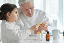 Sick Granddaughter With Grandfather Sitting At Home