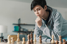 Smart Boy Playing Chess And Staring At The Chessboard