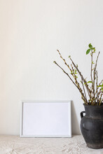 Home Decor Mock-up, Blank Picture Frame Near White Painted Concrete Wall , Black Earthenware Jug With Pussy Willow Branches And Blossoming Green Leaves