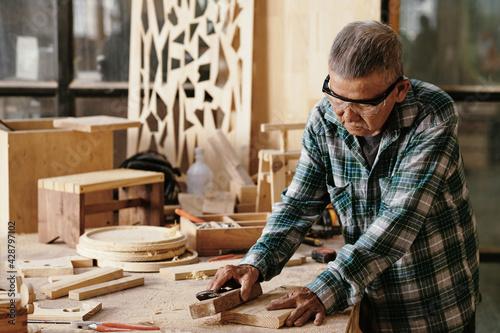 Fototapeta Senior carpenter polishing small board with wooden block at his workbench
