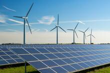Wind Turbine Energy Generators On Wind Farm, With Solar Panels Underneath.