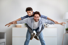 Playful Father And Son Having Fun Together, Daddy Riding Boy On Back Like Flying On Plane At Home In Living Room