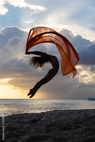 Fotografie, Obraz Silhouette of flexible fit woman jumping with silk during dramatic sunset with stormy clouds on the seascape background