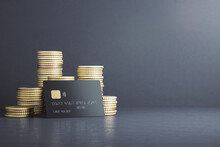 Investment Growth And Money Saving Concept With Black Credit Card In Front Of Stacks Of Coins On Dark Surface With Empty Background. 3D Rendering, Mockup