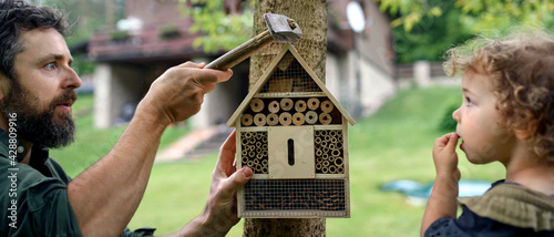 Canvas Small girl with father holding bug and insect hotel in garden, sustainable lifestyle