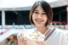 Coconut Ice Cream In Coconut Shell In Woman Hands Enjoying Eating, Thailand Street Food