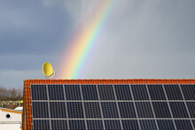 Rainbow Over A Tiled Roof With Solar Panels. Satellite Dish With A Smile .