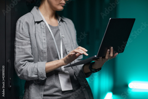Tela Cropped portrait of female data engineer holding laptop while working with super