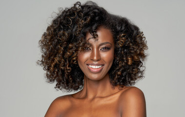 Portrait of happy african american woman with afro isolated on gray background