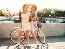 Two Young Beautiful Smiling Hipster Woman In Trendy Summer Sundress. Sexy Carefree Women Posing On The Street Background In Hats. Positive Models At Embankment At Sunset Near Bicycle