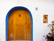 Picturesque Wooden Door, With A Blue Painted Frame, Mediterranean Style, With A Small Wooden Window On The Right Side.