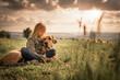 Beste Freunde - ein Kind lehnt sich an seinen Hund, einen Broholmer, an und beide genießen in der Natur den Sonnenuntergang an einem Spätsommertag