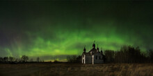 Vibrant Multi-colored Aurora (Northern Lights) Fill A Prairie Landscape Above A Dilapidated Abandoned Orthodox Church.