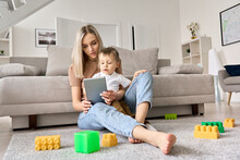 Young Mom Sitting At Home On Floor With Kid Of 3-4 Years Old, Watching Online Activities Classes For Early Education On Tablet, Or Movies Series For Kids Together.