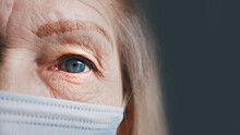 Eye Of A Senior Woman With Wrinkled Skin Under Medical Mask. Extreme Close Up. High Quality Photo
